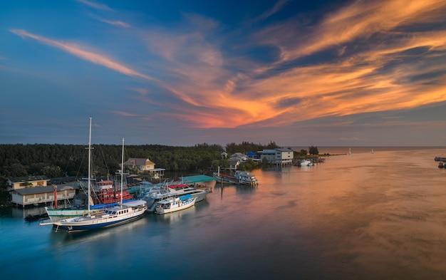 Barcos no porto do estuário com iluminação quente ao pôr do sol