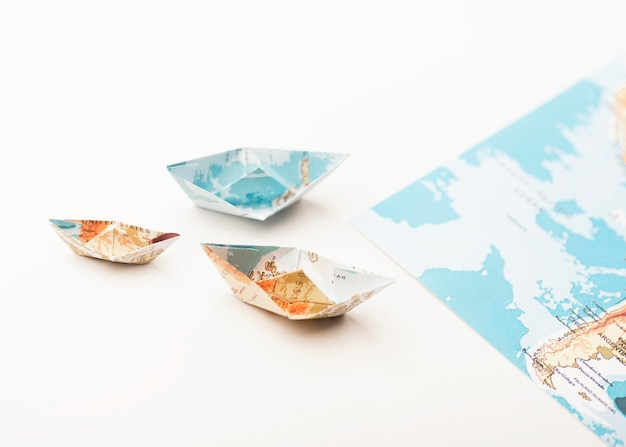 Barcos pequenos de papel de grande ângulo com mapas do mundo