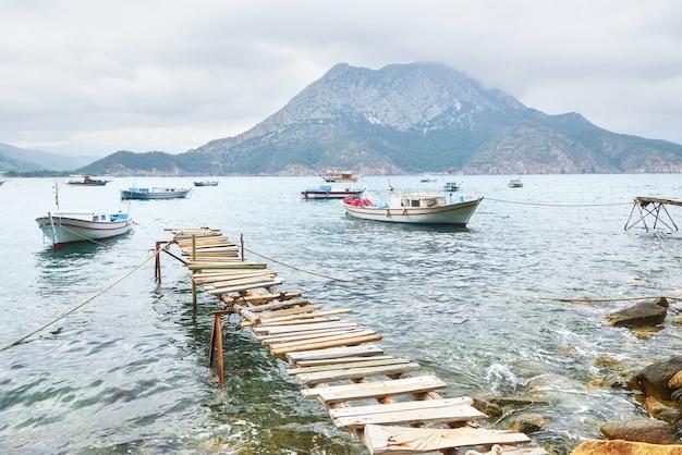Barcos perto do cais quebrado, colocando em uma água do mar azul tranquila e tranquila.