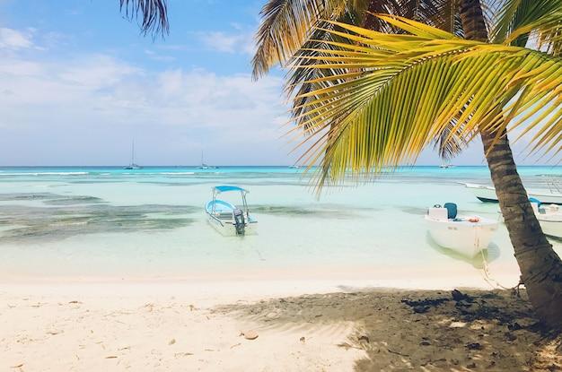 Barcos solitários em água azul-turquesa antes da praia dourada