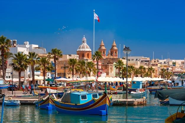 Barcos tradicionais de olhos coloridos luzzu na vila de pescadores mediterrânea de marsaxlokk, malta