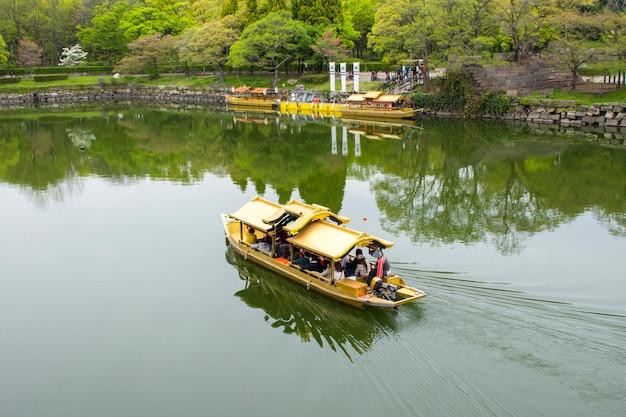 Barcos turísticos com turistas ao longo do fosso do castelo de osaka
