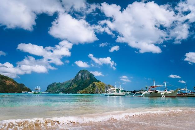 Barcos turísticos de recreio atracados perto da praia. ilha de cadlao no fundo, palawan, filipinas.