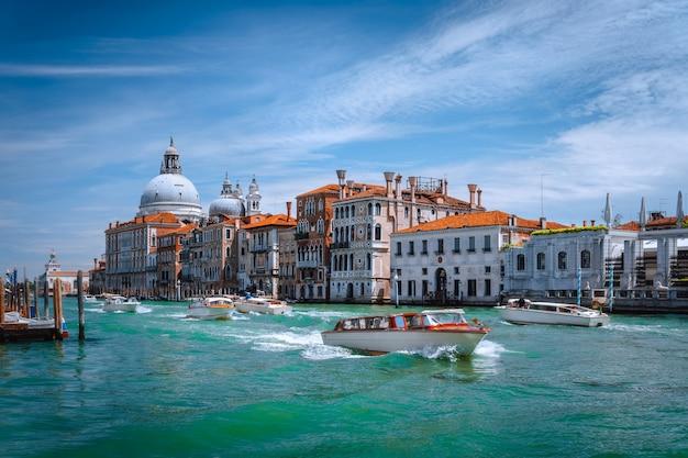 Barcos turísticos de recreio no grande canal e na basílica de santa maria della salute, veneza, itália