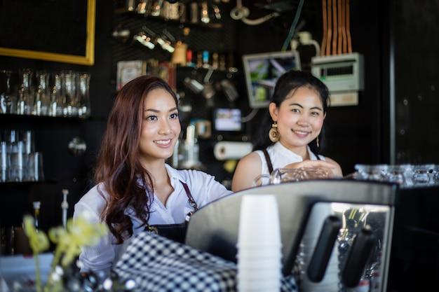 Barista asiático das mulheres que sorri e que usa a máquina de café no balcão da cafeteria - conceito do café da comida e bebida do proprietário de empresa de pequeno porte