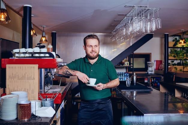 Barista barista com café na mão atrás do bar.
