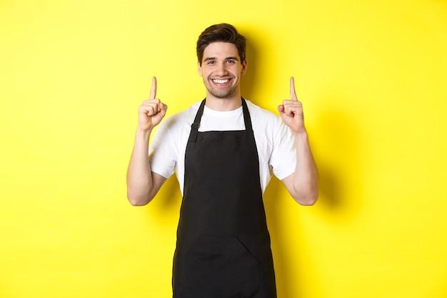 Barista bonito mostrando anúncio, oferta promocional de café, apontando o dedo para cima, em pé contra um fundo amarelo.