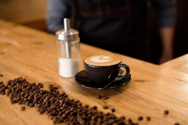 Barista bonito segurando uma xícara de café no café