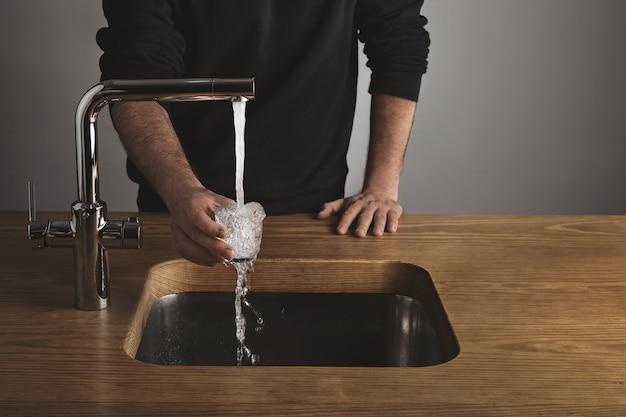 Barista brutal em um casaco preto atrás de uma mesa de madeira grossa enxagua um pequeno copo transparente com água sob uma torneira de metal prateado em um café. a água cai do vidro.