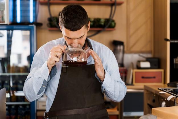 Barista cheira café aromatizado em uma cafeteira de vidro