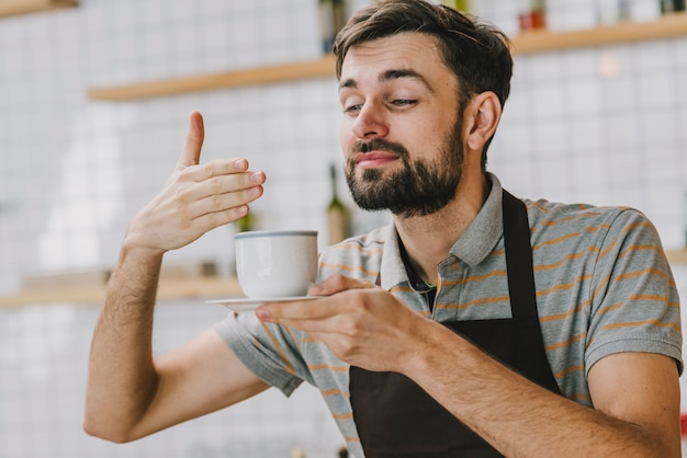 Barista cheirando a bebida quente