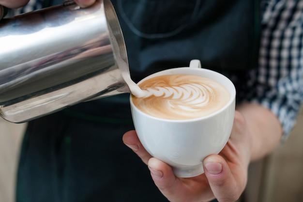 Barista com habilidade para servir café com cappuccino de leite