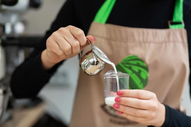 Barista de avental derrama o leite em uma xícara. barista trabalha em uma cafeteria