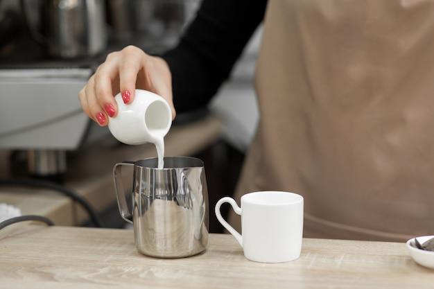 Barista de avental derrama o leite em uma xícara.