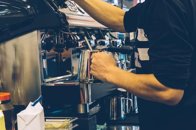 Barista de café no trabalho. fazendo o cappuccino ou o latte em uma máquina de café em uma cafetaria exterior.