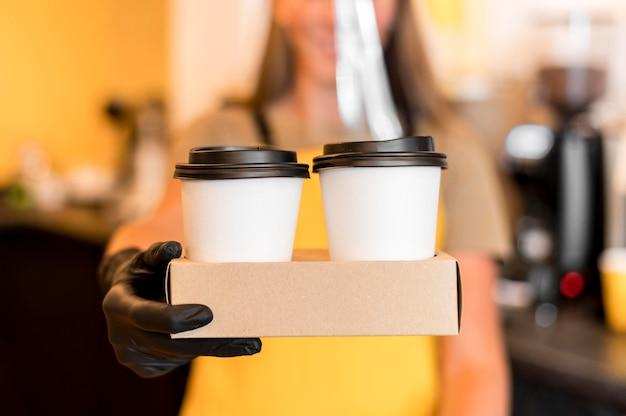 Barista de close-up com luvas servindo café