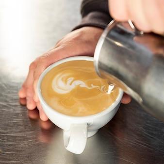 Barista de close-up, despejando uma xícara de café quente