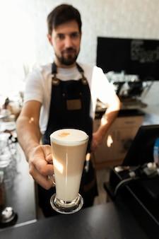 Barista de dose média segurando uma xícara de café