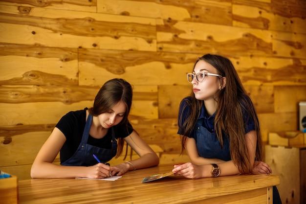 Barista de duas linda garota, sentado em uma mesa de madeira em uma casa de café
