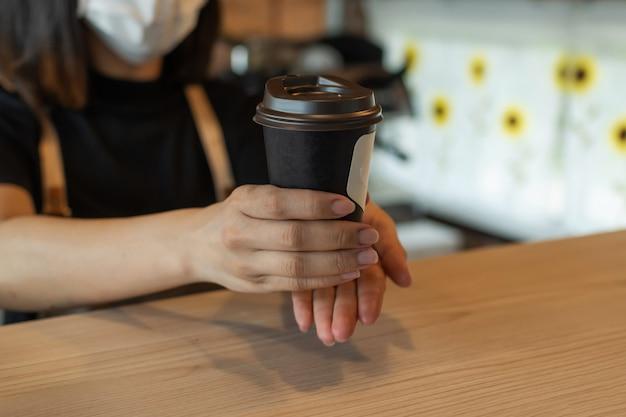 Barista de mulher amigável usando máscara protectora à espera de servir café preto gelo ao cliente no café café, restaurante café, mente de serviço, pequeno empresário, conceito de comida e bebida