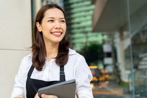 Barista de mulher asiática segurando o tablet para verificar a ordem do cliente