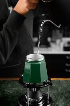 Barista de perto servindo água quente
