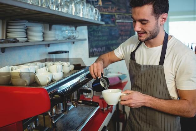 Barista derramando café na xícara no café