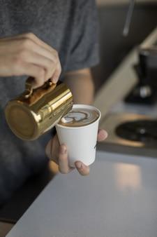 Barista derramar creme em um copo de cappuccino, fazendo uma bela arte de café