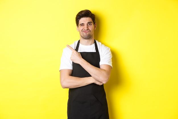 Barista descontente de avental preto apontando o dedo para o canto superior esquerdo, fazendo uma careta cética, não gosta de alguma coisa, de pé contra um fundo amarelo.