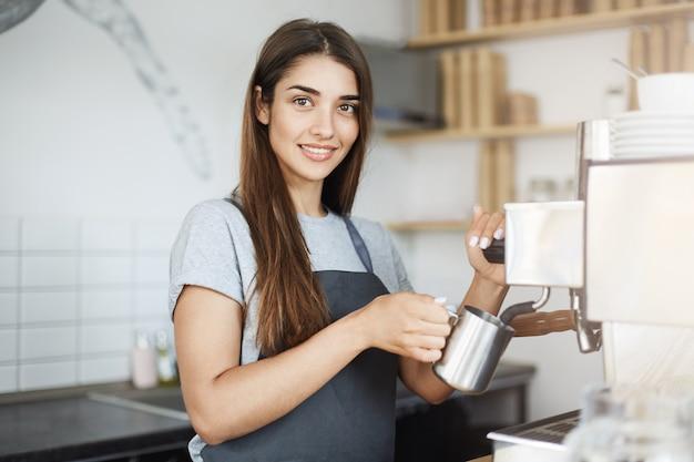 Barista experiente, desnatando leite em uma jarra, olhando para a câmera, sorrindo