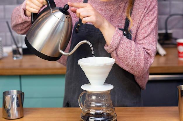 Barista faz café expresso usando um funil. o processo de fazer café no provador