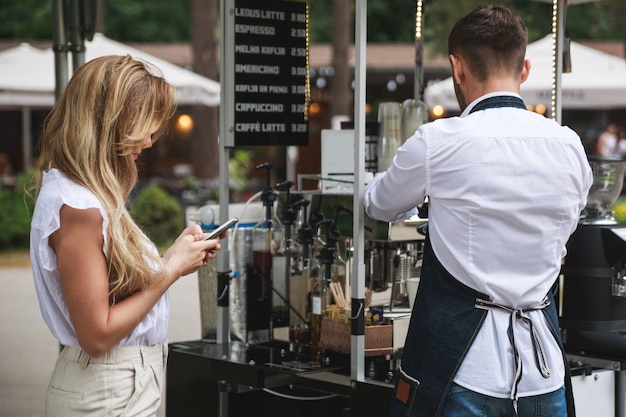 Barista fazendo café para o cliente em sua cafeteria móvel de rua