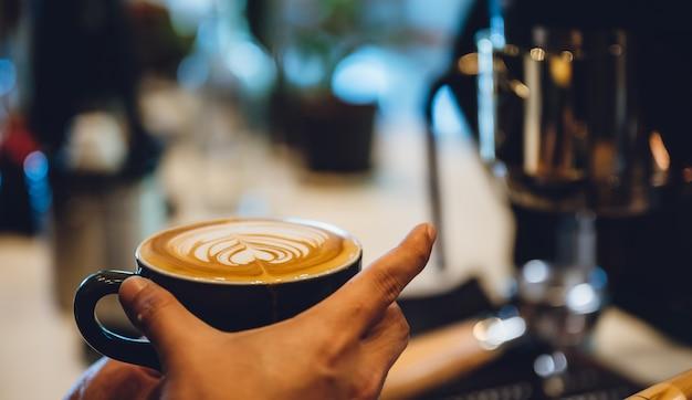 Barista fazendo latte art, tiro foco em xícara de leite e café