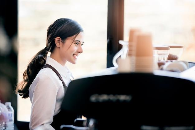 Barista fêmea bonito no uniforme que está e que trabalha com máquina de café.