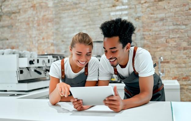 Barista feminina branca e barista masculina africana ficam com um tablet nas mãos atrás de um balcão em uma cafeteria.