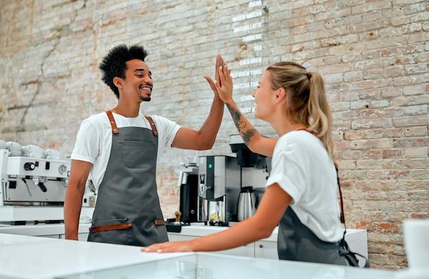 Barista feminina caucasiana e barista masculina africana fazendo gesto de mais cinco atrás do balcão em uma cafeteria.
