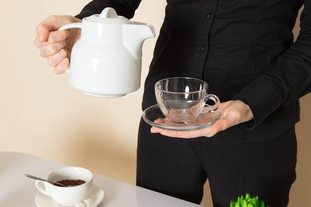 Barista feminino em calças de camisa preta com ingredientes de equipamento de café marrom chá seco na parede branca