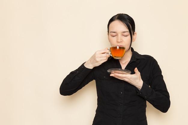 Barista feminino em calças de camisa preta com ingredientes de equipamento de chá marrom café seco fazendo e bebendo chá na parede branca
