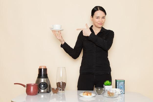 Barista feminino em calças de camisa preta em frente a mesa com equipamento de ingredientes de café na parede branca