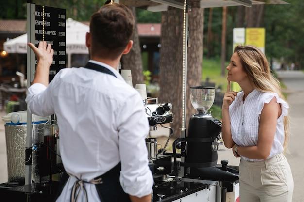 Barista homem se oferece para escolher vários tipos de café para a cliente mulher em seu café móvel