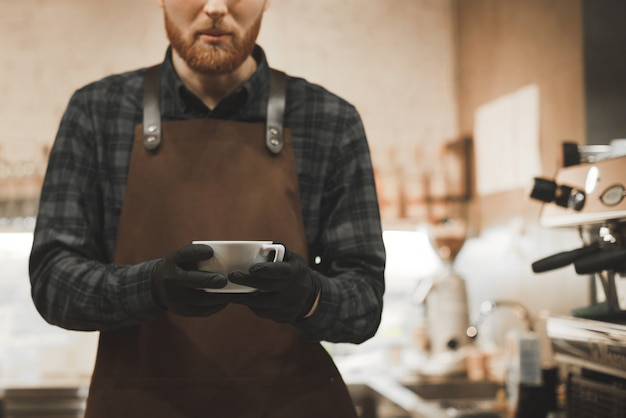 Barista homem trabalha no café acolhedor e segura uma xícara de café perfumado.