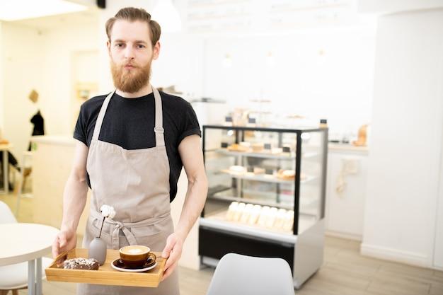 Barista jovem bonito carregando bandeja com cappuccino