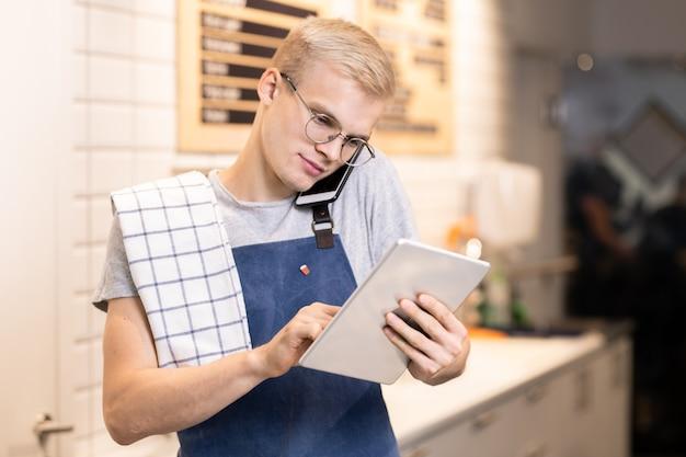 Barista jovem e contemporâneo de avental segurando o smartphone pela orelha enquanto consulta um dos clientes e rola no touchpad