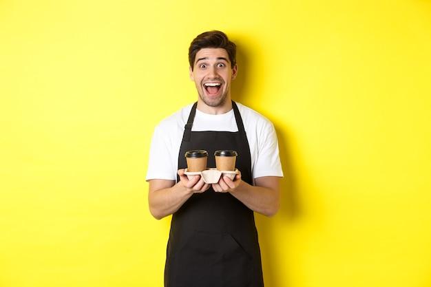 Barista masculino animado segurando duas xícaras de café para viagem, trabalhando no café, em pé sobre um fundo amarelo.
