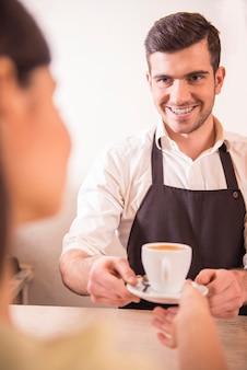 Barista masculino bonito, esticando a mão com uma xícara de café
