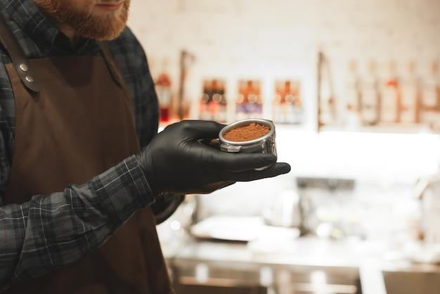Barista masculino com barba segurando um porta-filtro e preparando café em sua cafeteria