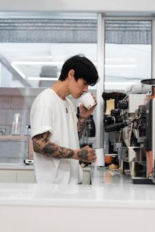 Barista masculino com tatuagens com cheiro de café moído na hora na xícara
