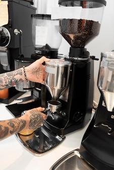 Barista masculino com tatuagens trabalhando na máquina de café