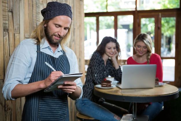 Barista masculino escrevendo pedidos com clientes do sexo feminino em segundo plano em uma cafeteria