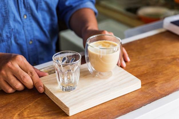 Barista masculino serve café com leite quente e água fresca em copo no bar balcão de madeira.